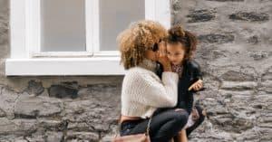 babysitter whispering into girl's ear