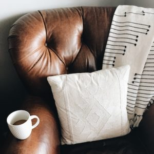 Cozy home chair with white pillow and cozy blanket
