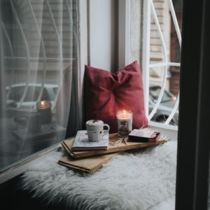 Cozy home corner with candle and books