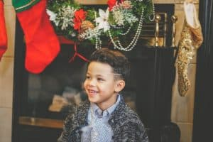 smiling boy by Christmas mantle