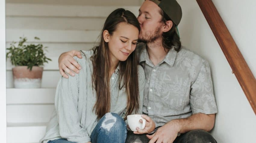 Husband kissing wife on head