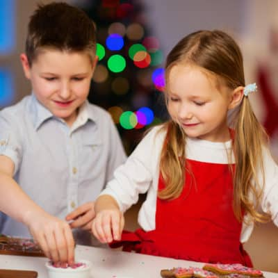 boy and girl decorating cookies as a Christmas tradition