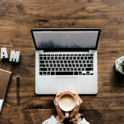 woman with laptop holding coffee