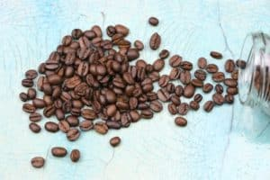 coffee beans spread out on turquoise countertop