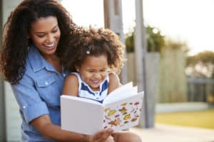 Girl and mom reading book and laughing