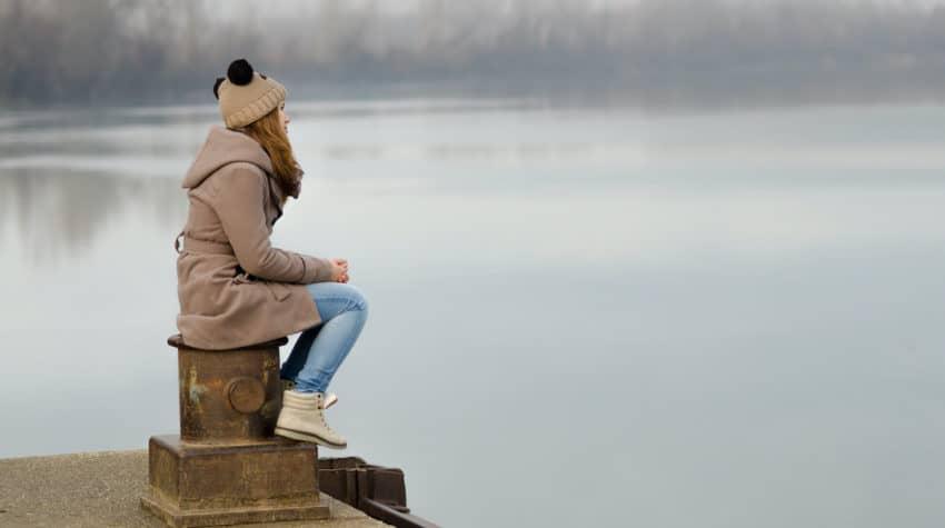 Woman staring sadly at a lake