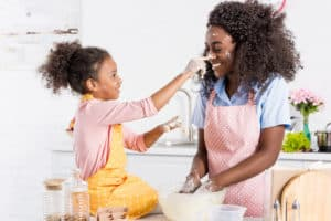 mom and girl having fun in kitchen