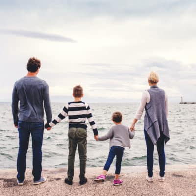 family staring at the ocean and holding hands
