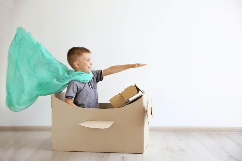 boy pretending to be superhero in a cardboard airplane
