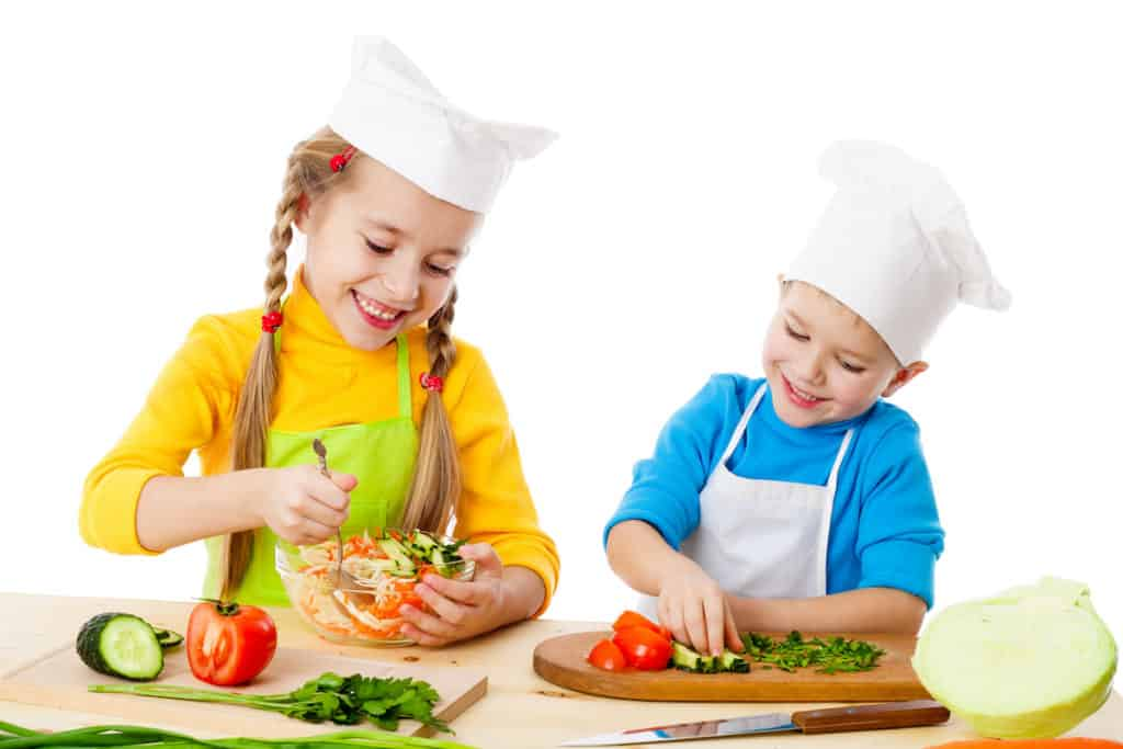 two kids in chef hats making a salad