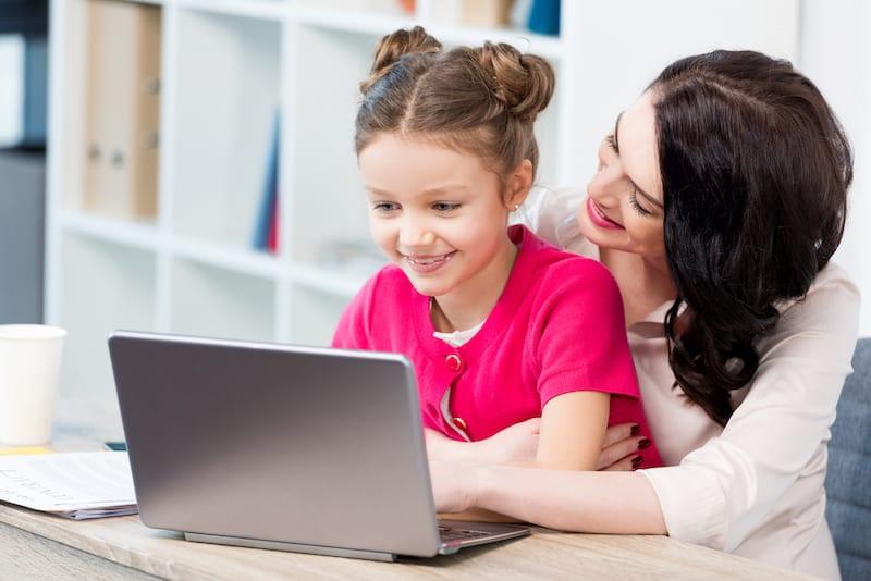 girl sitting on moms lap looking at laptop