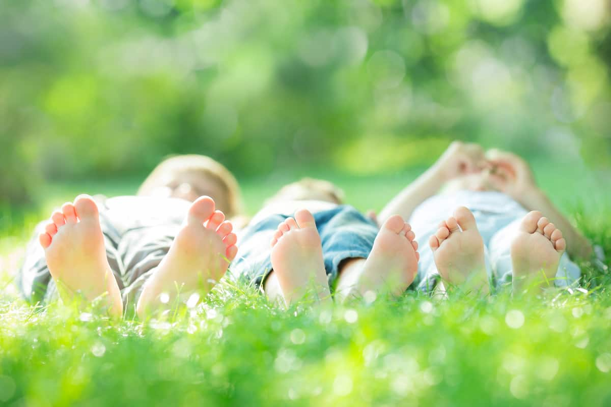 happy family with bare feet lying on green grass in spring
