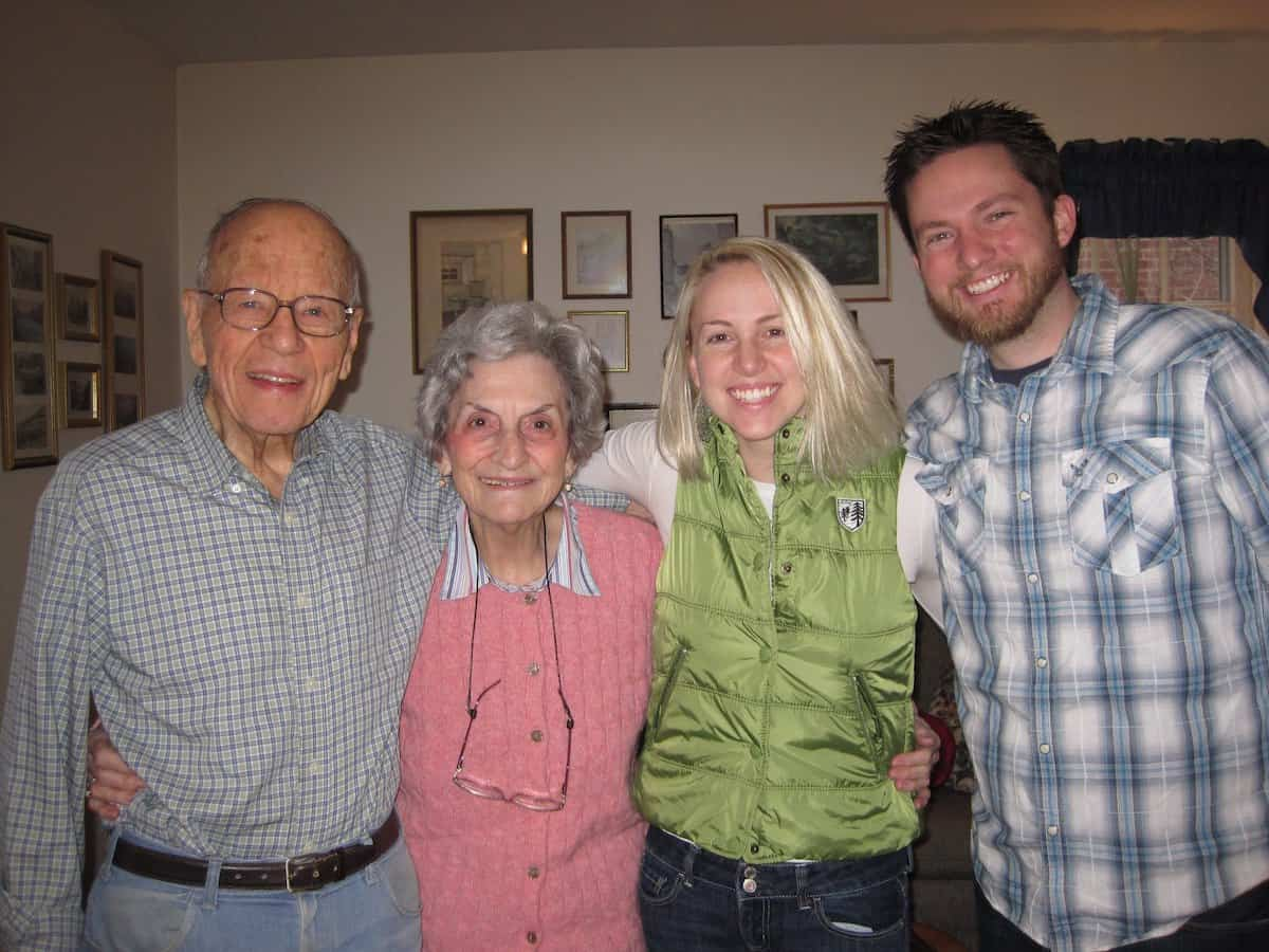 Grandparents smiling and arm around young married couple