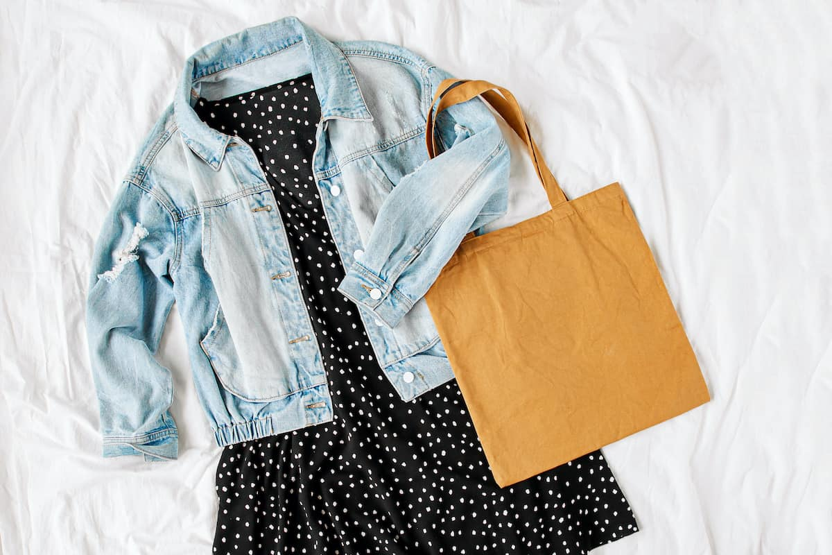 Blue jean jacket and black dress with tote bag on white bed. Women's stylish autumn or spring outfit. Trendy clothes. Flat lay, top view.