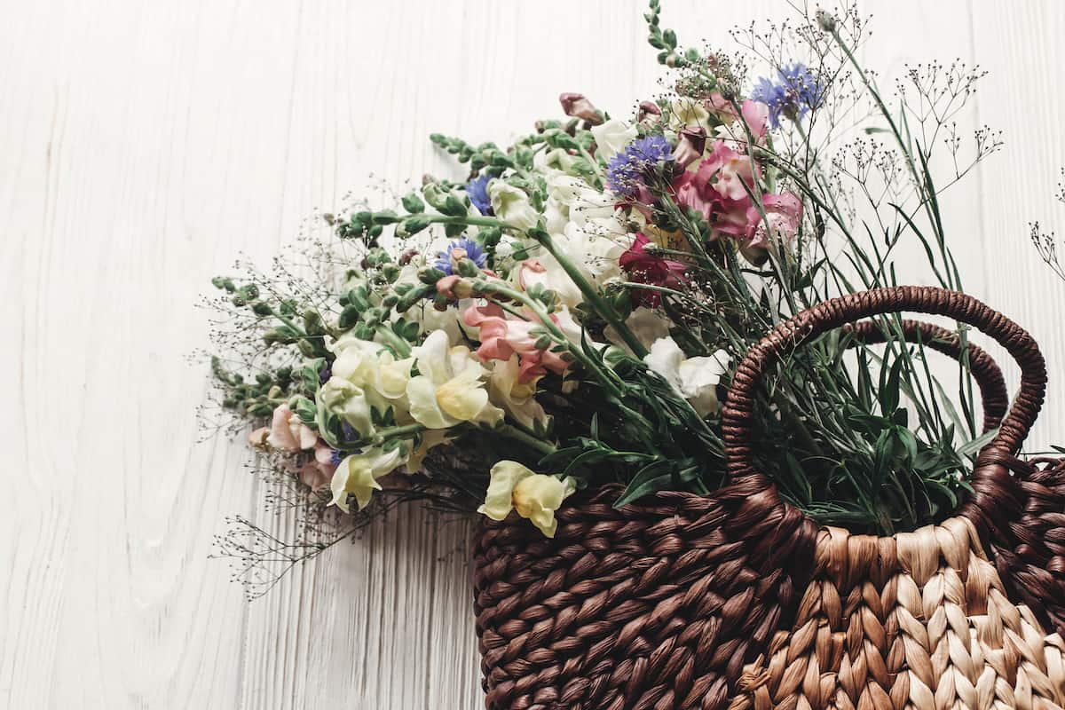 beautiful woven basket filled with wildflowers on a white wood background