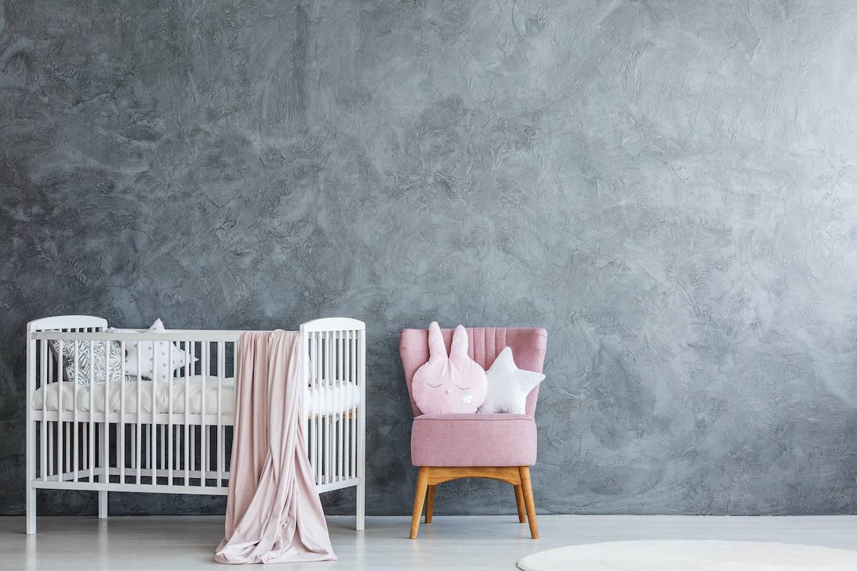 empty white crib against gray wall in baby nursery
