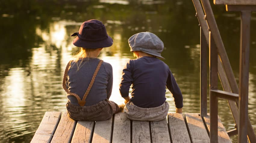 2 kids sitting on a dock in summer