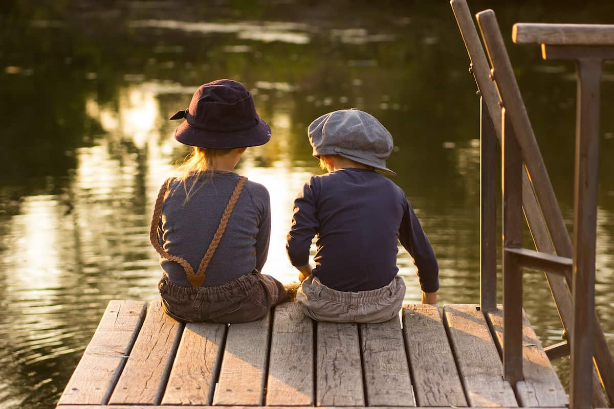 two kids sitting on a dock fishing