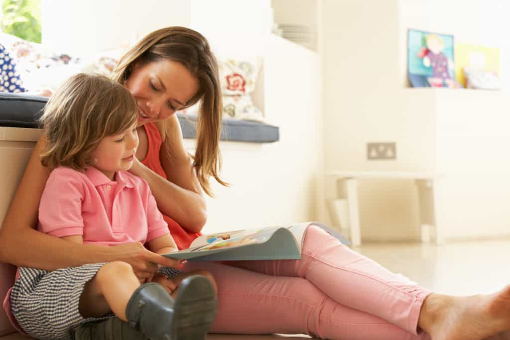 Mother Sitting With Son Reading Story Indoors.