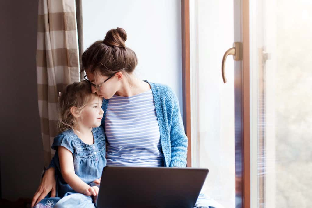 Mother working on computer holding daughter.