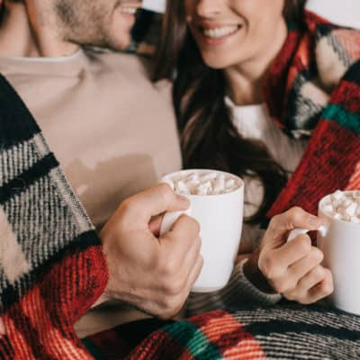 married couple snuggling with holiday blanket and sipping hot cocoa