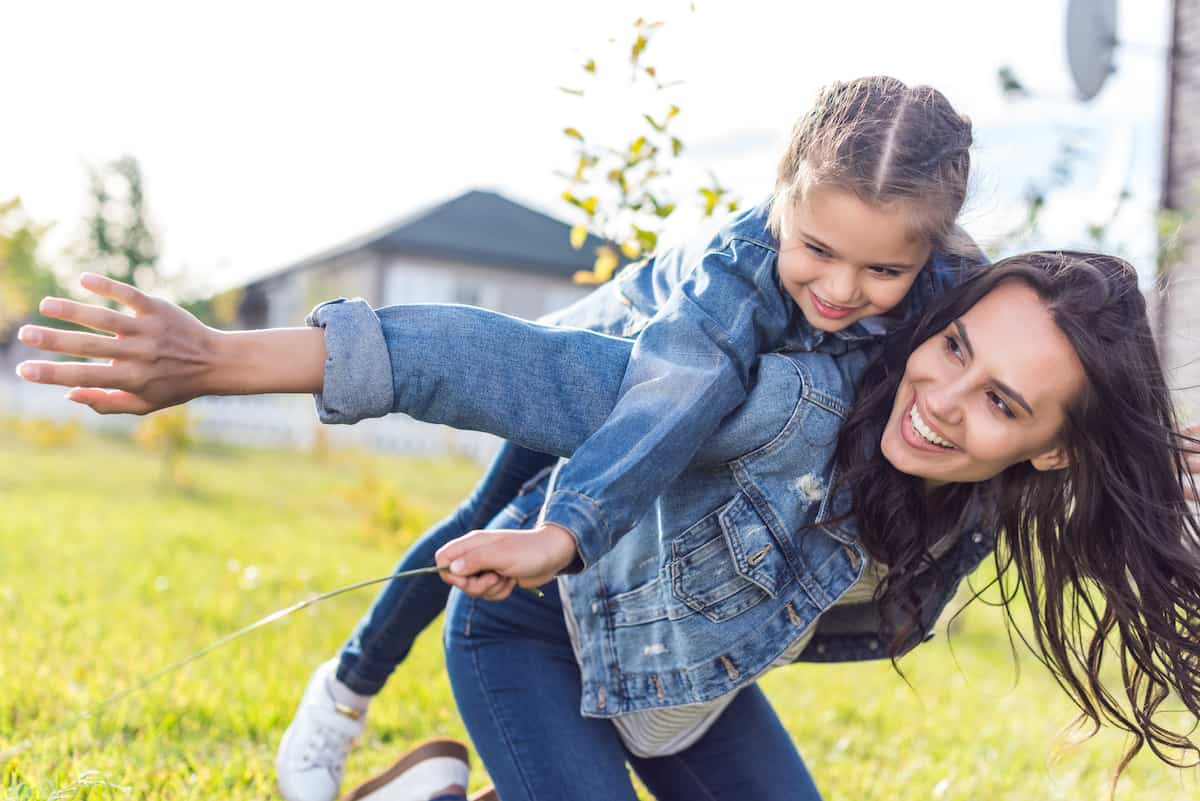 Mom smiling as she gives her daughter a piggyback ride outside