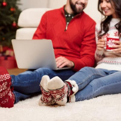 couple smiling at each other holding Christmas mug and laptop