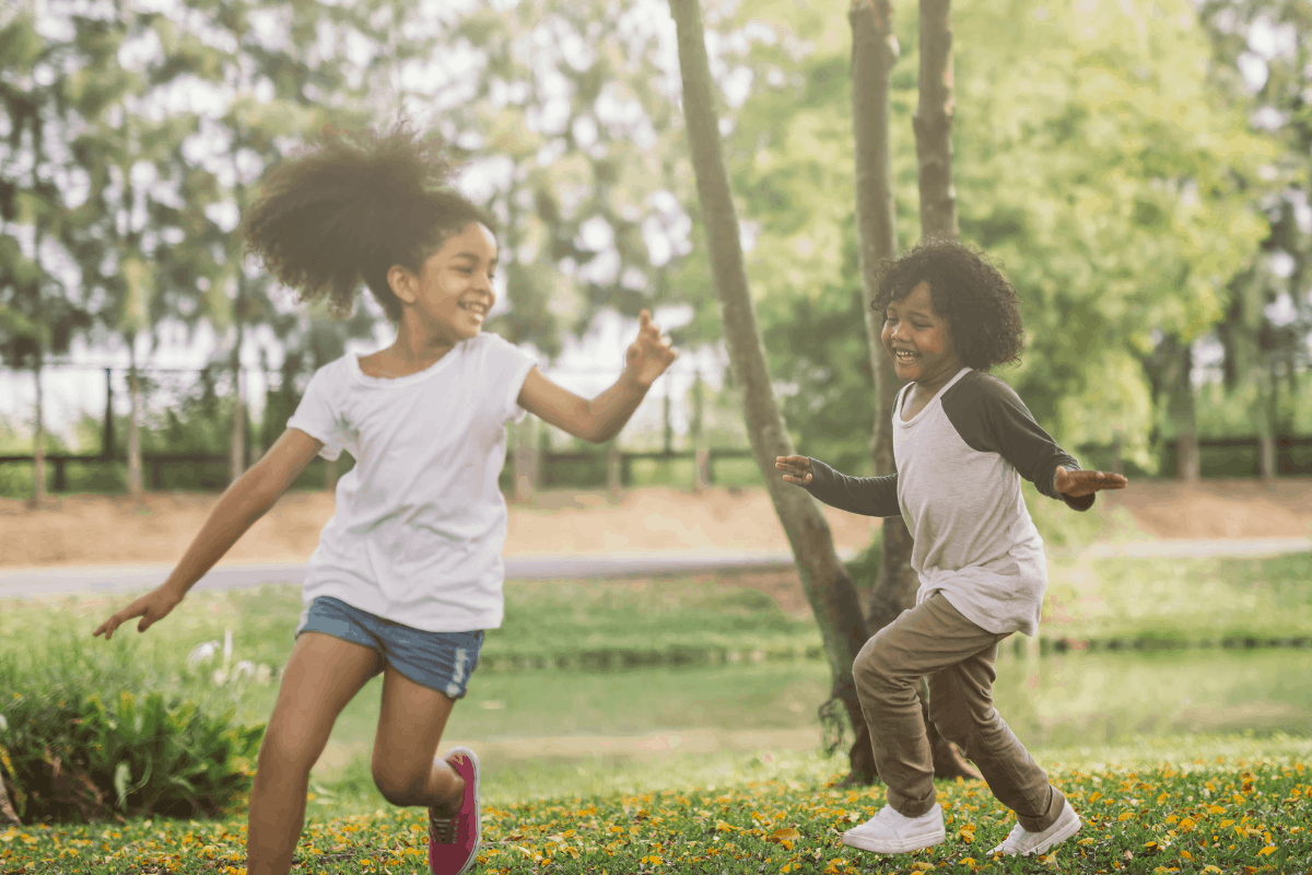 two kids running and smiling in the green grass